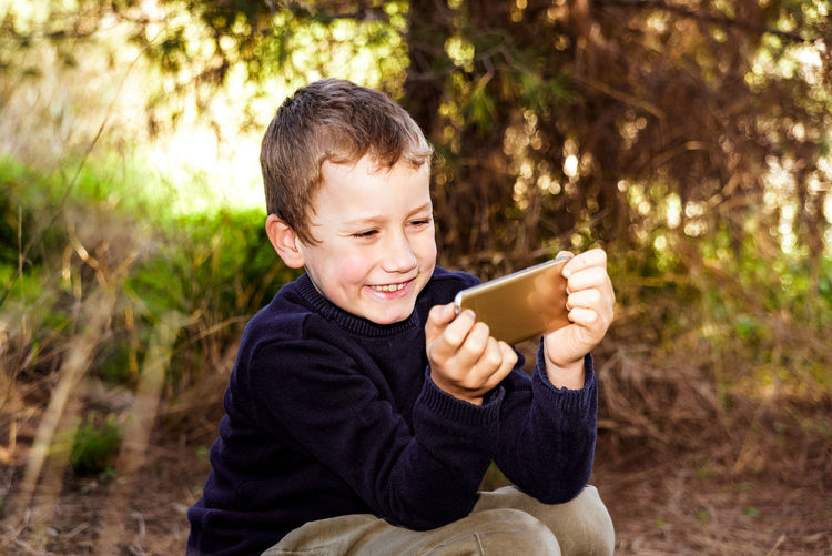 Portrait of boy holding smart phone outdoors