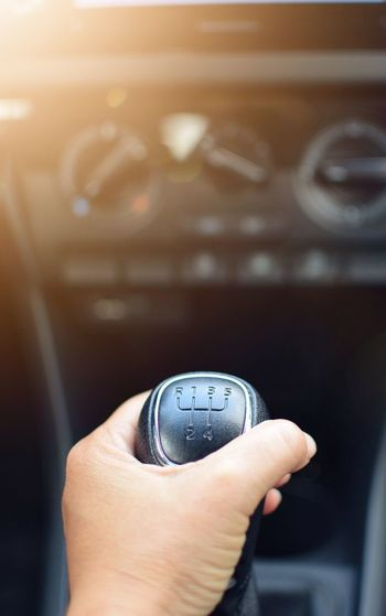 Cropped hand of person holding gearshift while driving car