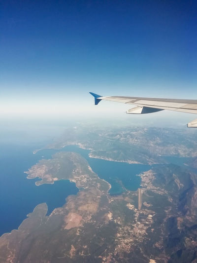 Aerial view of airplane flying over sea against blue sky