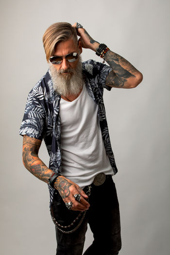 Portrait of a bearded hipster isolated on a white background Bearded Beard Posing Tattoo Tattooed Model Modern Cut Out Studio Shot Attractive Sunglasses Hairstyle Rocker Hipster Biker Standing Leisure Activity Jeans Jewelry Mustache Confident  Thoughtful Men Mature Adult People