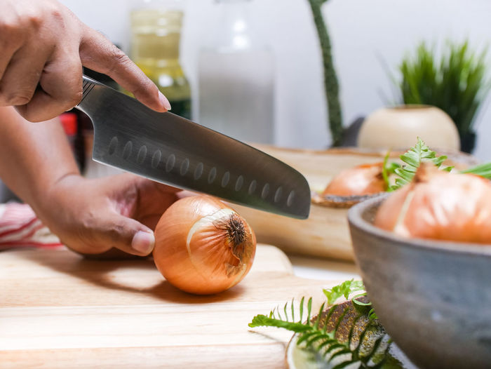 Cropped hands cutting onion on table