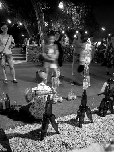 Onlookers watch as the talented young boy skillfully stacks the glass bottles. Lifestyles Street Full Length Shadow Night Person Outdoors Capture The Moment EyeEm Best Shots Street Photography Bottles Collection Bottle Stacks Art
