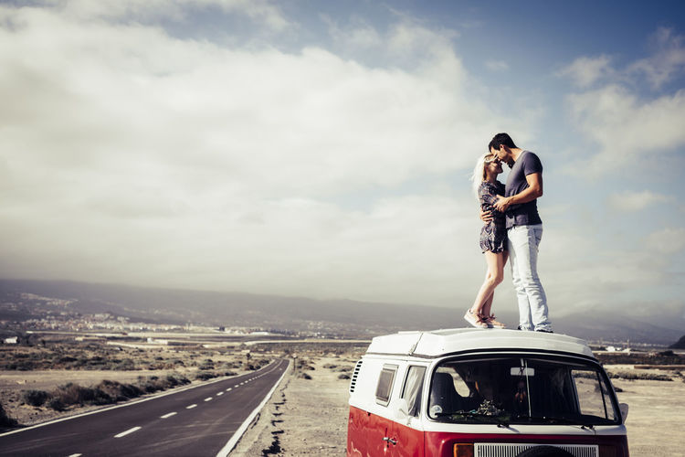 Couple Embracing On Van By Road Against Sky