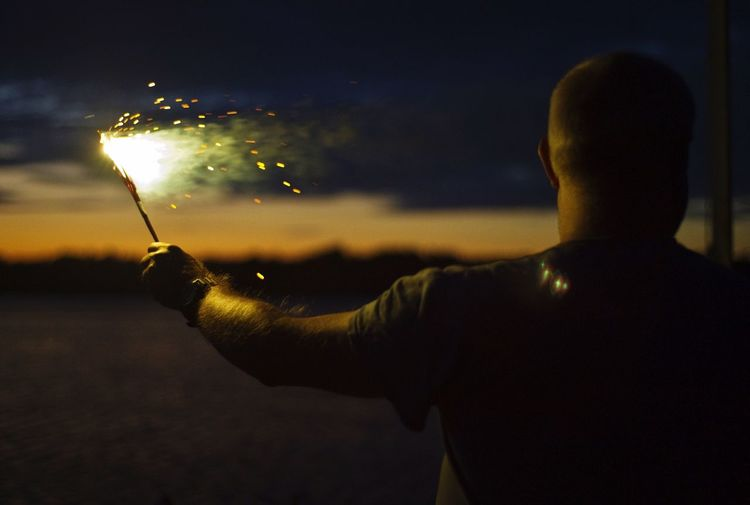 Rear View Of Man Holding Sparkler On Field At Night