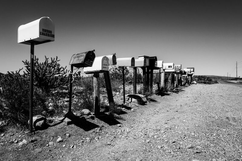 Mailboxes In A Row By Field Against Sky