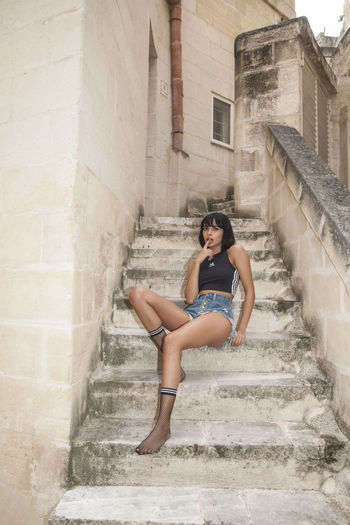 Full length portrait of woman sitting on staircase against building