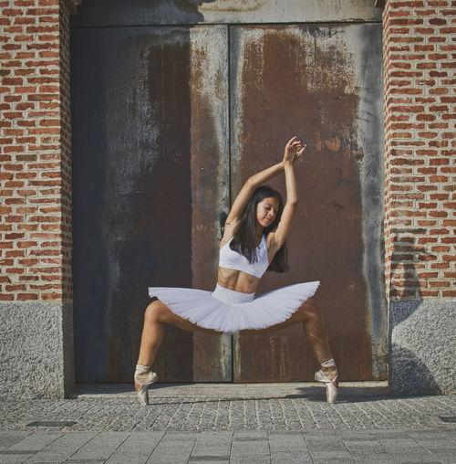 Ballerina sitting on seat against brick wall
