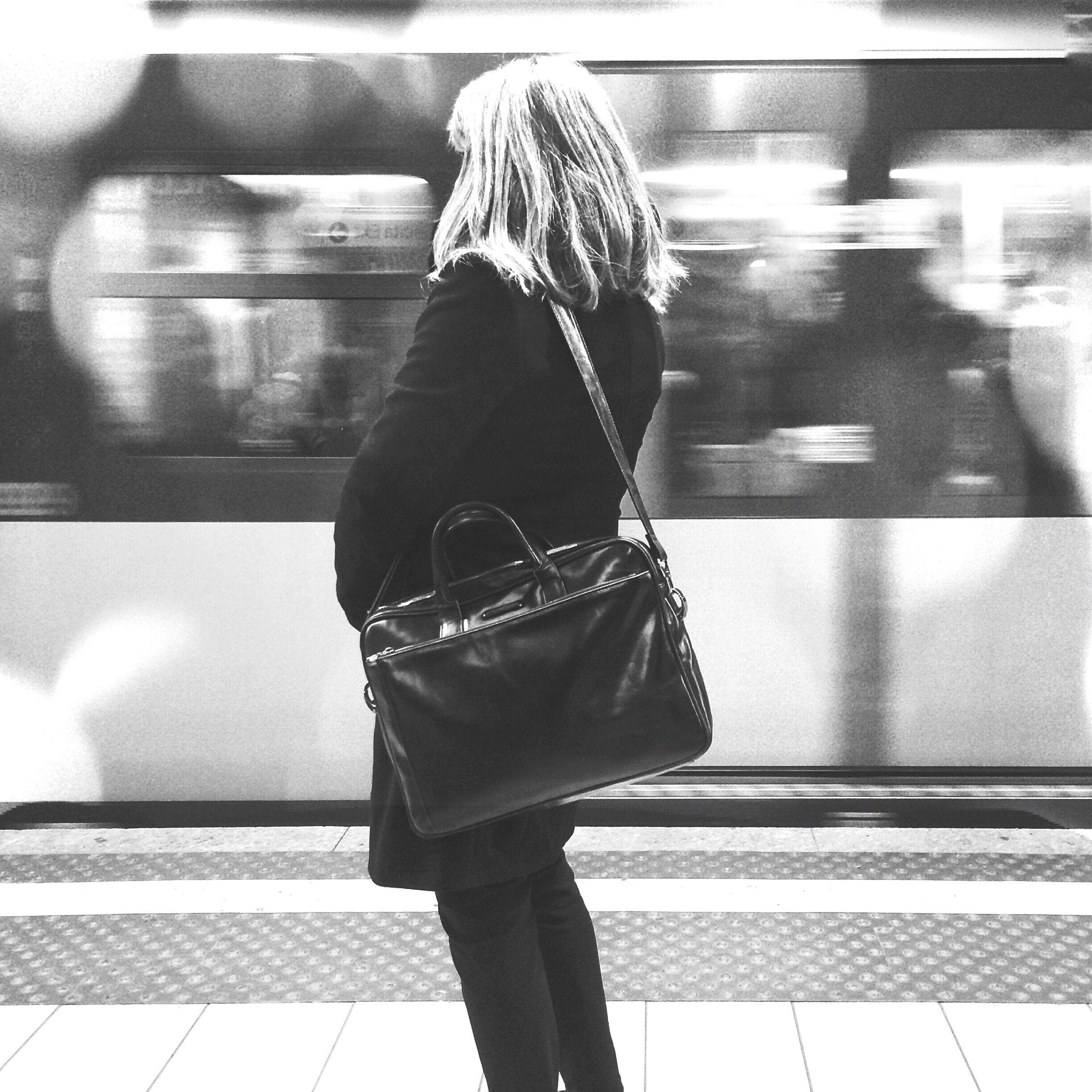 indoors, lifestyles, standing, full length, rear view, casual clothing, person, blurred motion, walking, railroad station, men, leisure activity, illuminated, motion, railroad station platform, subway station, city life, public transportation