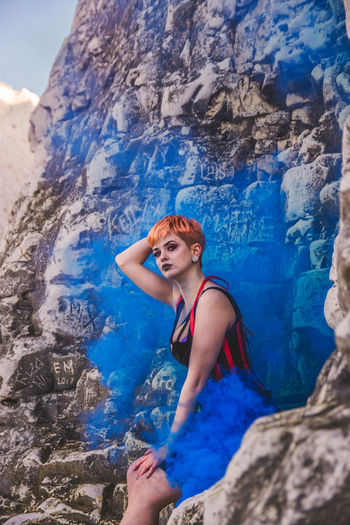 Low angle view of young woman on rock formation