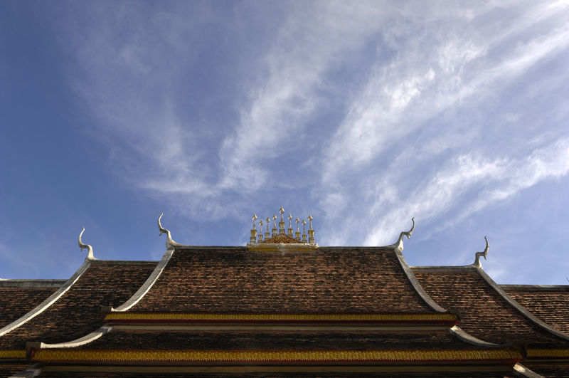 Low angle view of traditional building against cloudy sky on sunny day