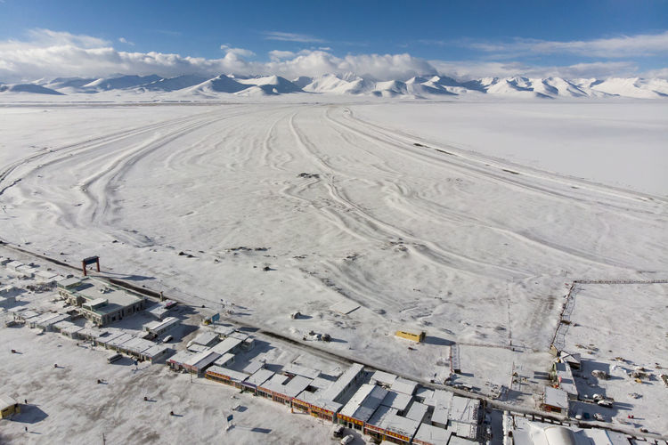 Frozen Namtso during early April before spring approaches. Namtso was born in the Paleogene age, as a result of Himalayan tectonic plate movements. The lake lies at an elevation of 4,718 m (15,479 ft), and has a surface area of 1,920 km2 (740 sq mi). This salt lake is the largest lake in the Tibet Autonomous Region. It is renowned as one of the most beautiful places in the Nyainqêntanglha mountain range. Tibetan Buddhism Wanderlust Blue China Cloud - Sky Cold Temperature Environment High Angle View Hill Lake Mountain Mountain Range Namtsolake Nature Pilgrimage Scenics - Nature Snow Snow Mountain Snowcapped Mountain Tibet Travel Destinations Water Winter