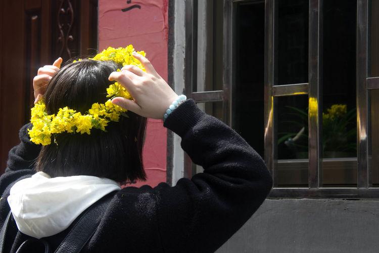 Rear view of woman wearing flower tiara in front of window