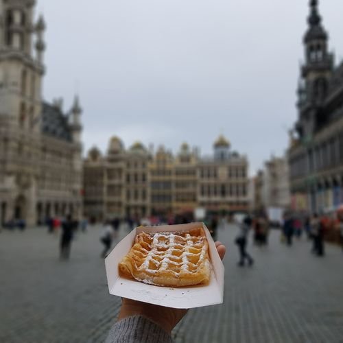 Belgian waffle in the middle of Brussels Brussel Brussels Belgium Belgium Waffle Waffle Food Travel Human Hand City Women Incidental People Christmas Decoration Sky Close-up Architecture Food And Drink Town Square Old Town