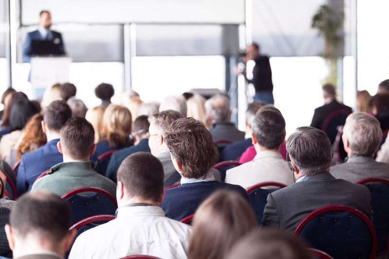 Unrecognizable participants at a business conference listening to the presentation Large Group Of People Group Of People Business Presentation Conference Conference Room Participant Audience Listening Sitting Coaching Public Event Seminar Symposium Auditorium Speech Speaker Presenting Training Corporate Corporate Event