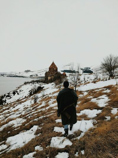 Rear view of man walking on snow covered landscape