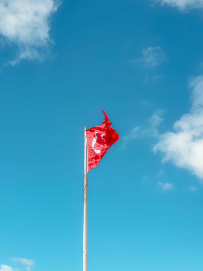 Low angle view of flag on pole against blue sky