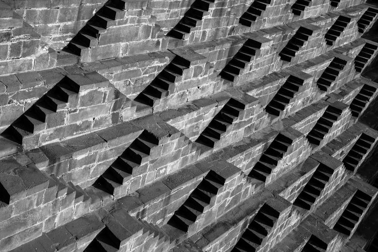 Light and shadow play at the step well of Chand Baori Backgrounds Blackandwhite Light And Shadow No People Pattern Steps Well Stone Steps Textured