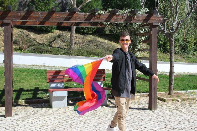 Full length of a smiling man holding rainbow flag