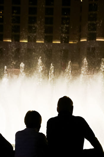 Rear view of silhouette people against illuminated water at night