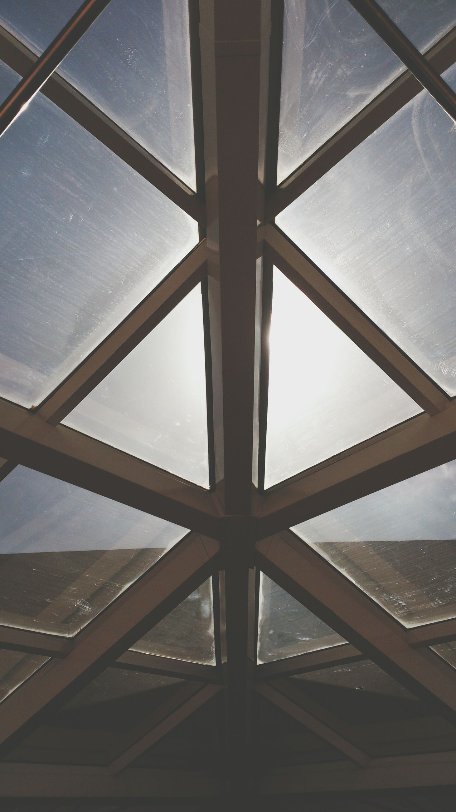 low angle view, architecture, built structure, indoors, ceiling, glass - material, window, directly below, pattern, sky, architectural feature, skylight, modern, transparent, geometric shape, building exterior, day, full frame, design, no people