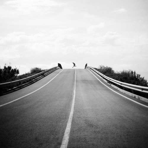 Side view of man jumping on empty road against sky