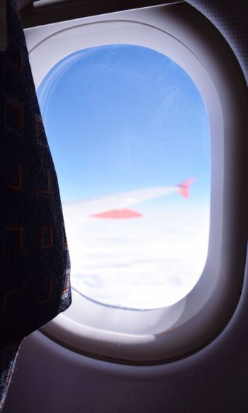 Close-up of airplane wing against sky seen through window