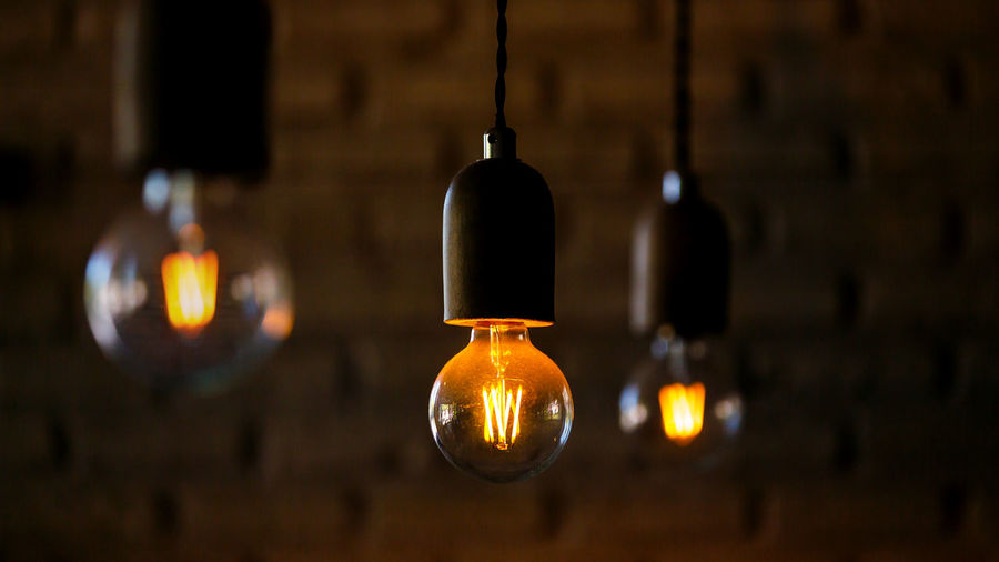 Close-up of illuminated light bulb hanging against wall