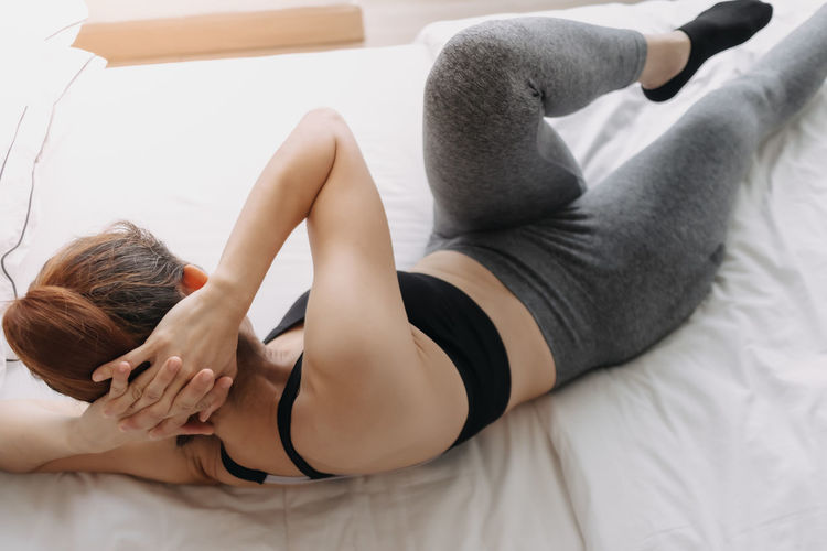 Rear view of woman lying on bed at home