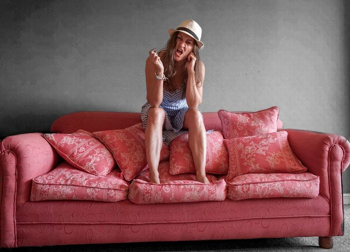 Young woman making face on sofa at home