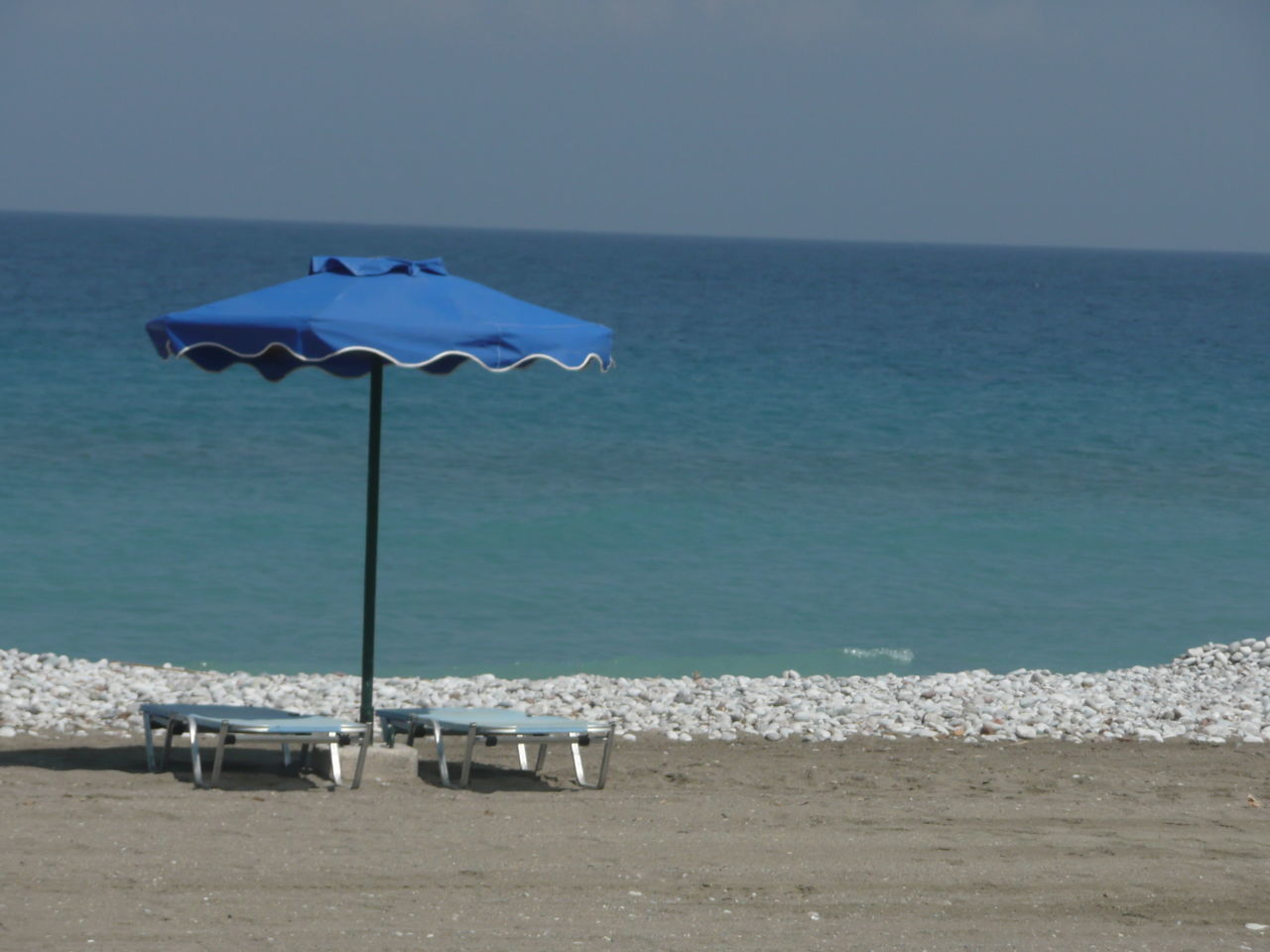 Parasol And Lounge Chairs At Beach