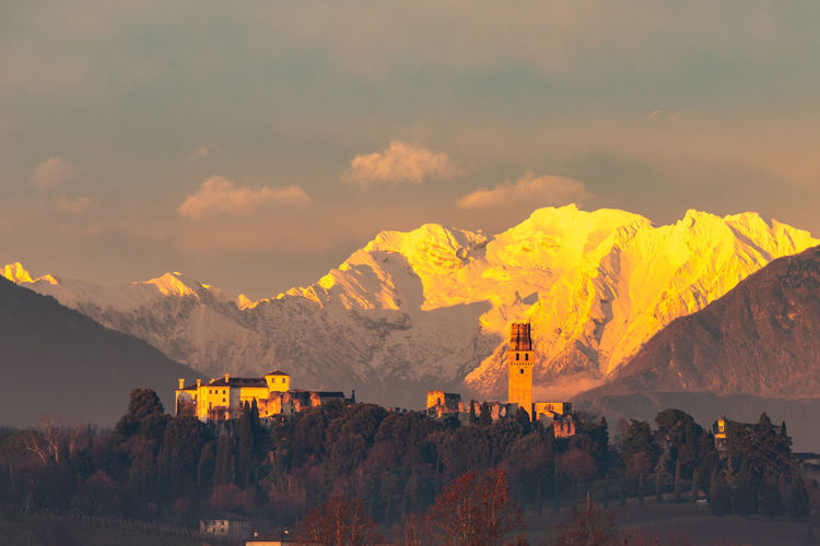 Panoramic view of buildings and mountains against sky during sunset
