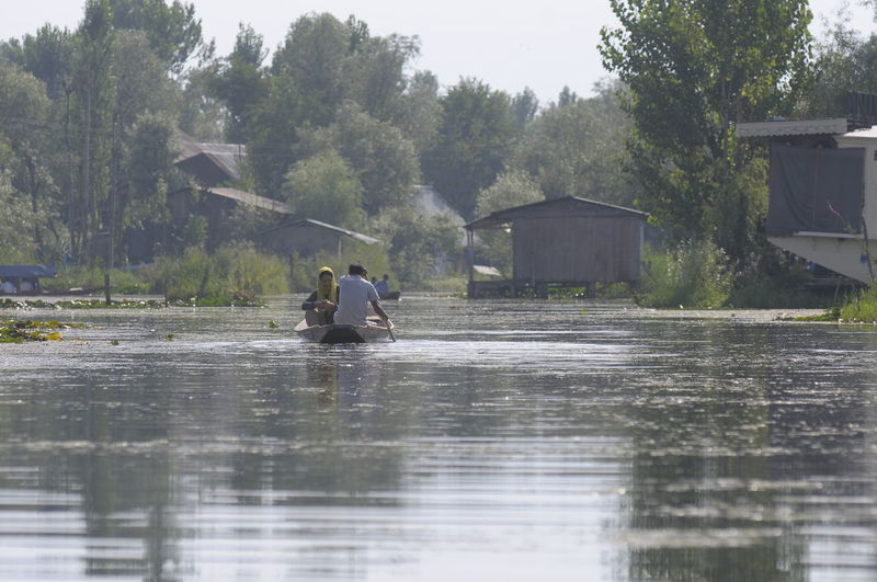 local people in kashmir using a boat to travel Water Waterfront Tree Nature Day Plant Lake Architecture Reflection Transportation Men Real People Outdoors People Built Structure Sky Mode Of Transportation Building Exterior Rain