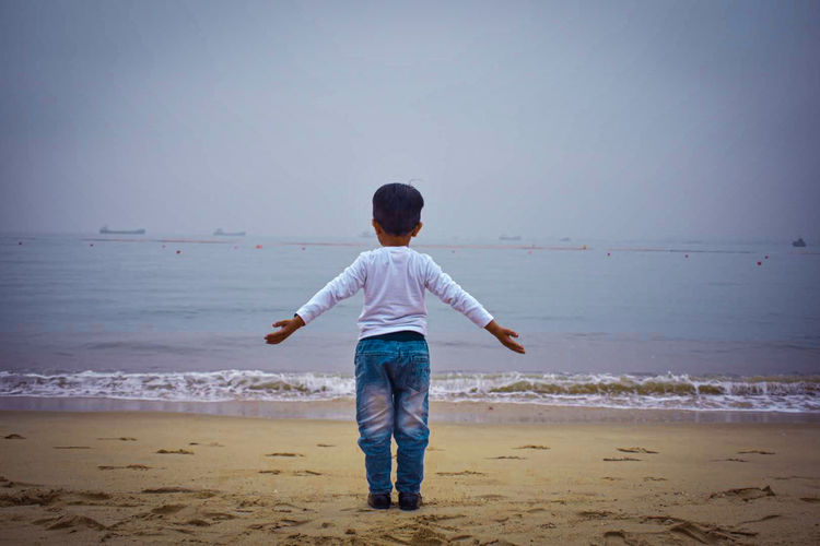 Rear view of child standing on beach