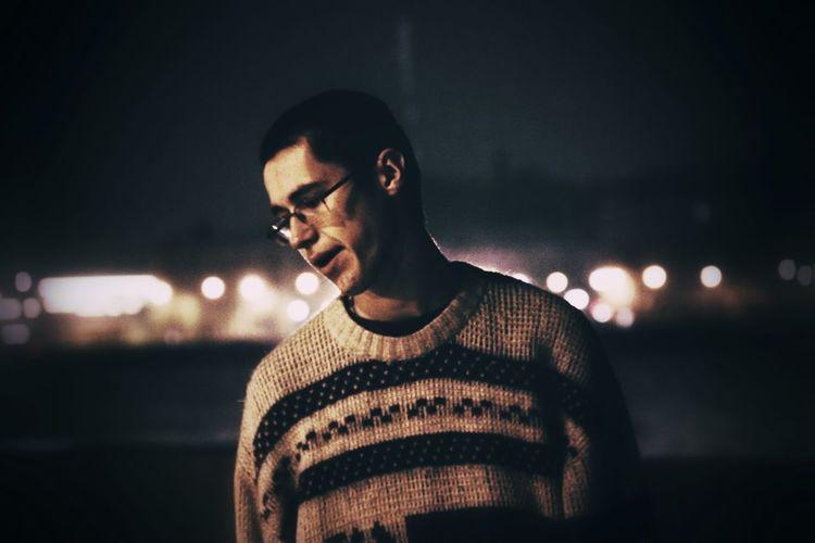 Young man looking away at night
