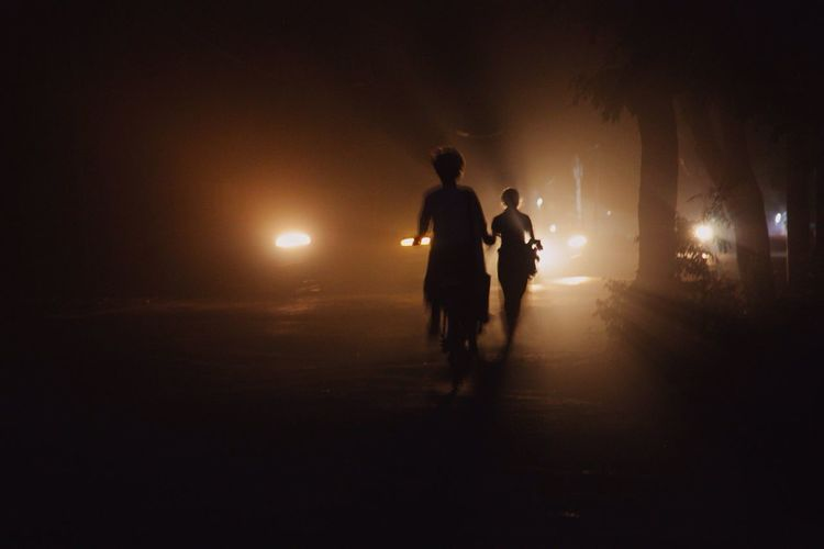 Silhouette People On Illuminated Street At Night