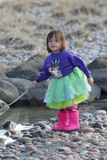 Full length of girl standing on pebbles