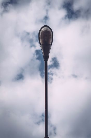 Directly below shot of street light against cloudy sky