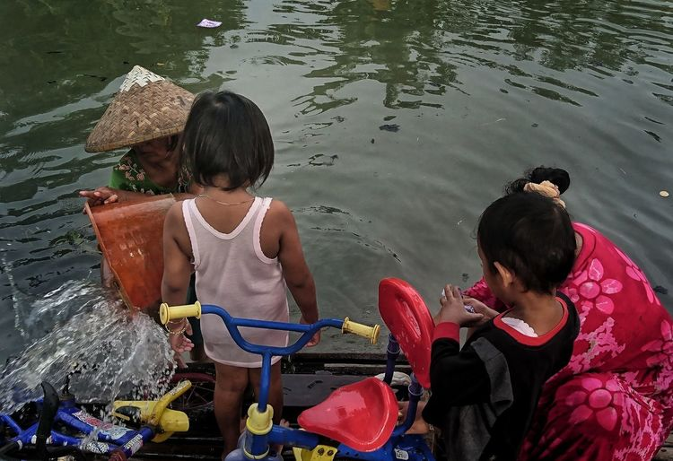Citizen use the river water for daily activities River Sanitation Sanitary Riverflow Polution Polution On Water Daily Activities Daily Life Cikarang West Java  INDONESIA Water Child Togetherness Sitting Girls Childhood High Angle View Sari