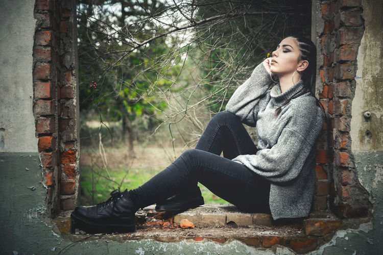 Full Length Of Young Woman Posing While Sitting At Abandoned Building