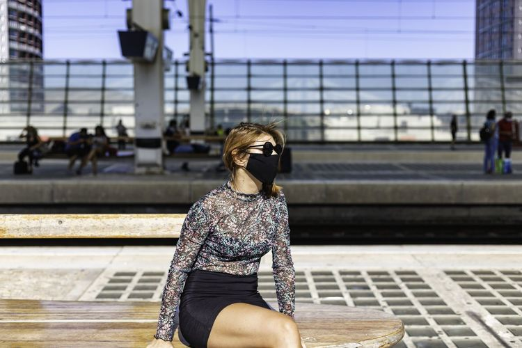 Full length of woman sitting at railroad station
