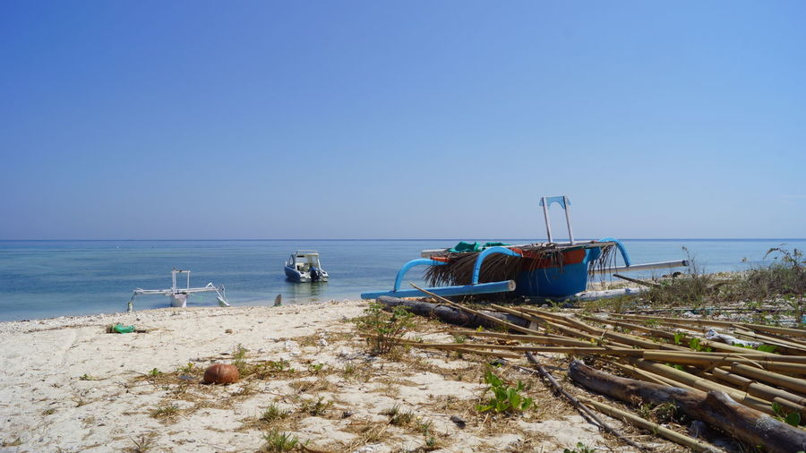 Outrigger canoe moored at beach against clear sky on sunny day