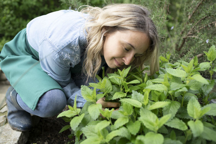 Young woman smiling with plants