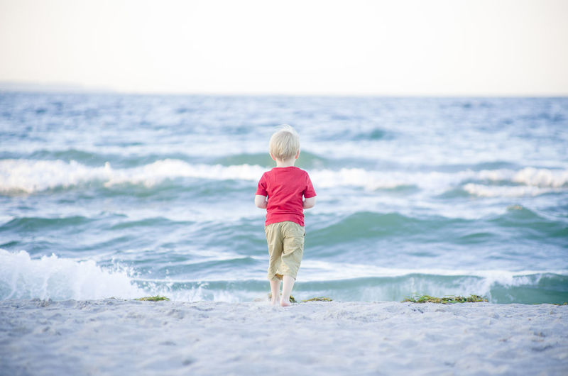 Rear view of blond boy standing at beach
