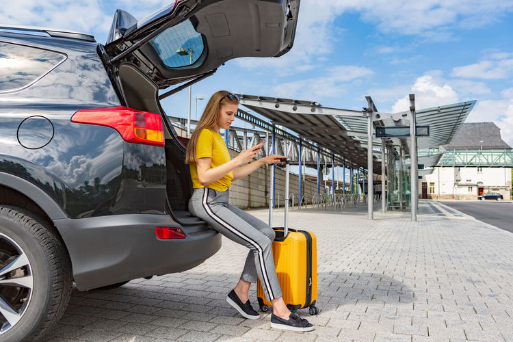Side view of teenage girl using mobile phone while sitting with luggage on car trunk