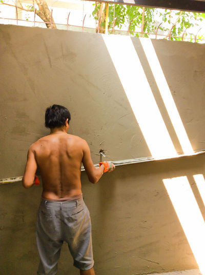 Rear view of shirtless worker working at construction site