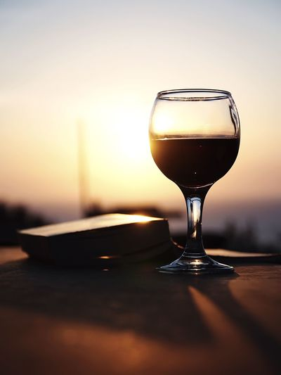 Close-up of wineglass on table against sky during sunset