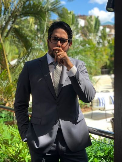 Well-dressed mid adult man smoking cigar while standing in park