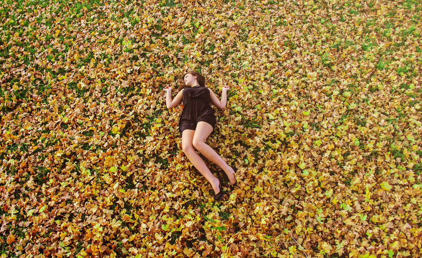 High Angle View Of Woman Lying On Grass