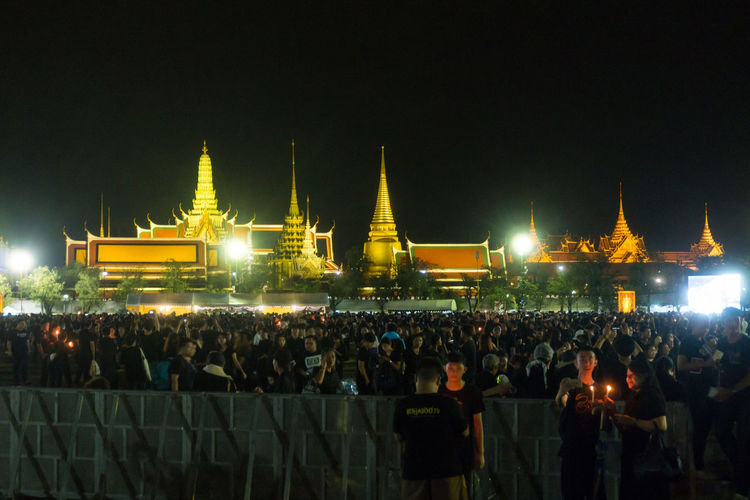 Crowd at illuminated temple against sky at night