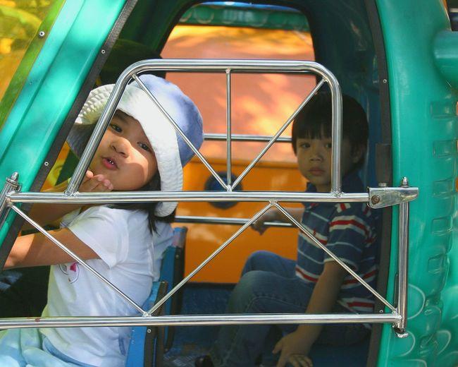 Portrait of siblings sitting in amusement park ride